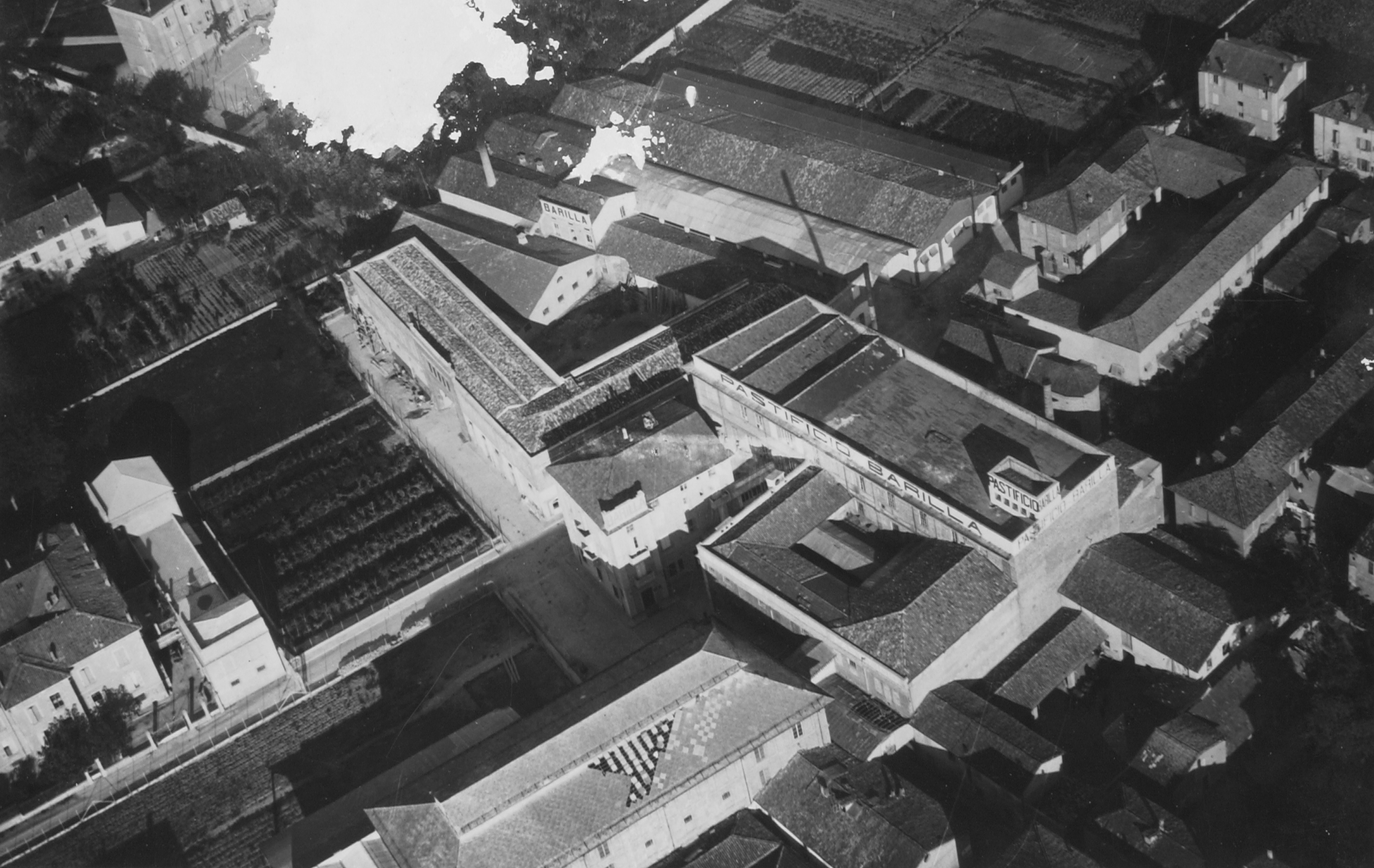 Aerial view taken from the south-west by the NAIS of Siena, after 1930 [ASB, A210]. It is possible to recognize the pasta plant at the center expanding around a small central courtyard which would be covered later; the bakery with its exposed brick facade