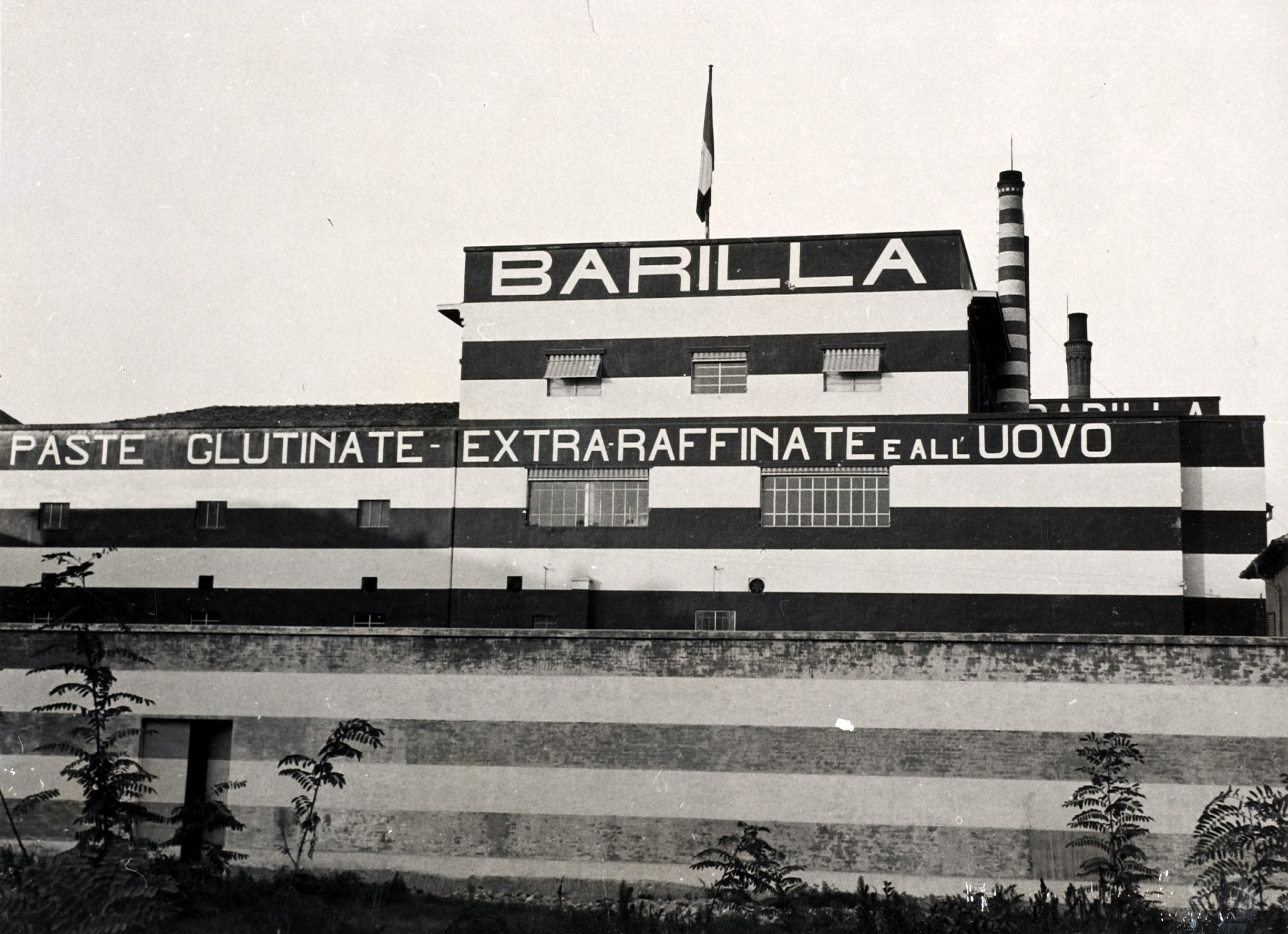 The factory's south facade, characterized by the painted signs and by a chromatic styling with red and white stripes, in a photo dating back to 1930 [ASB, A 106].