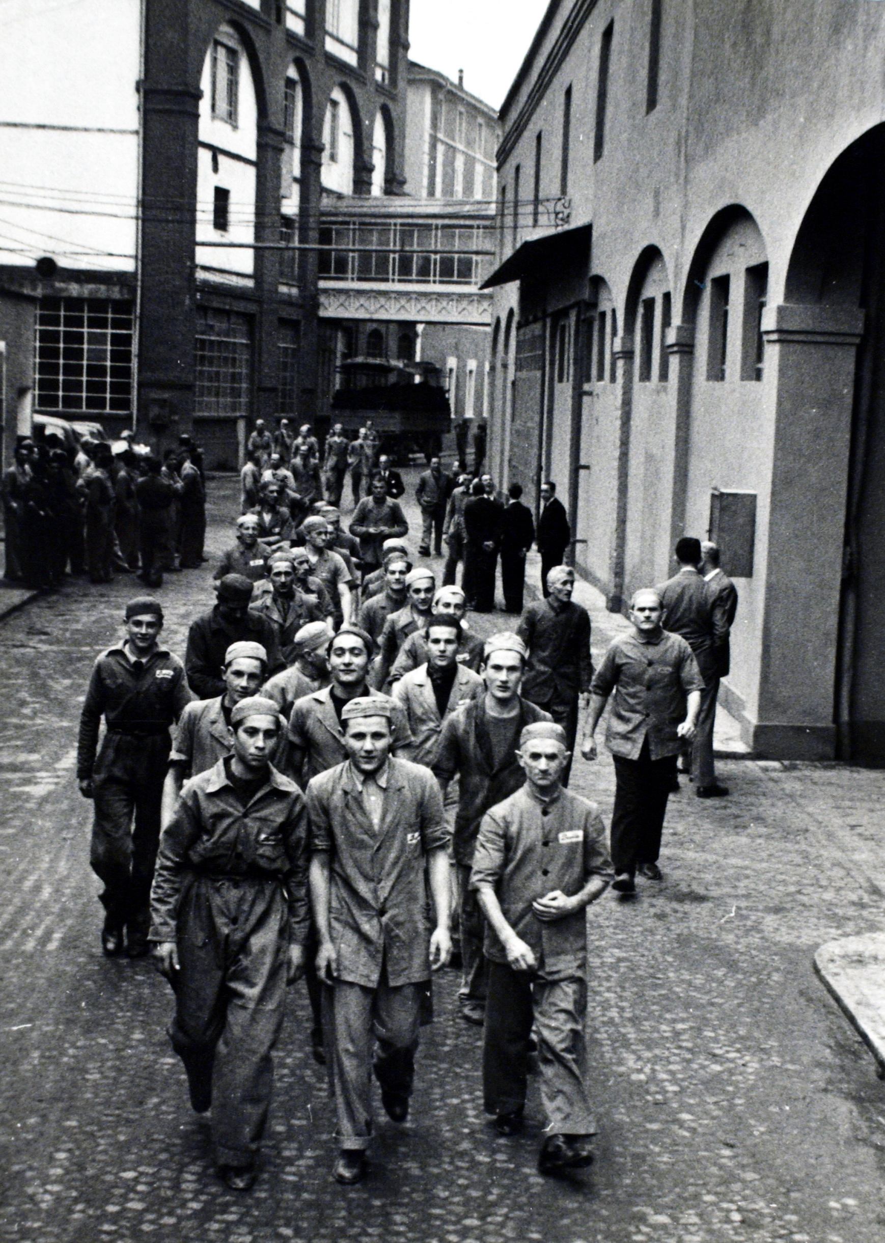 A view of the passage between the bakery (on the right) and the pasta plant (on the left) and workers walking through during the change of shift in 1940 [ASB, Aa 563].