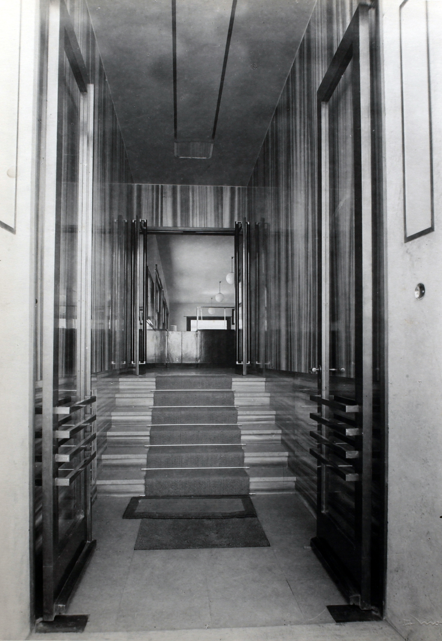 The entrance of the offices designed on the ground floor of the building by the architect Elsässer in a photo taken by Alberto Montacchini in 1934 [ASB, Aa 134].