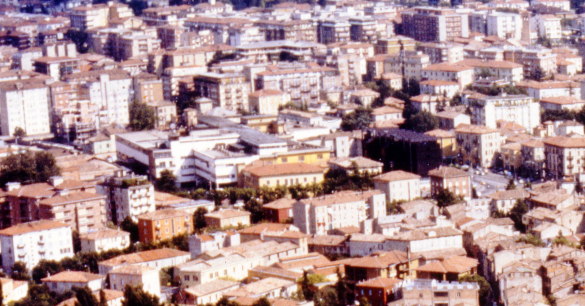 Aerial view facing South-West of the suburbian neighborhoods of the city of Parma with the Barilla plant in the center.