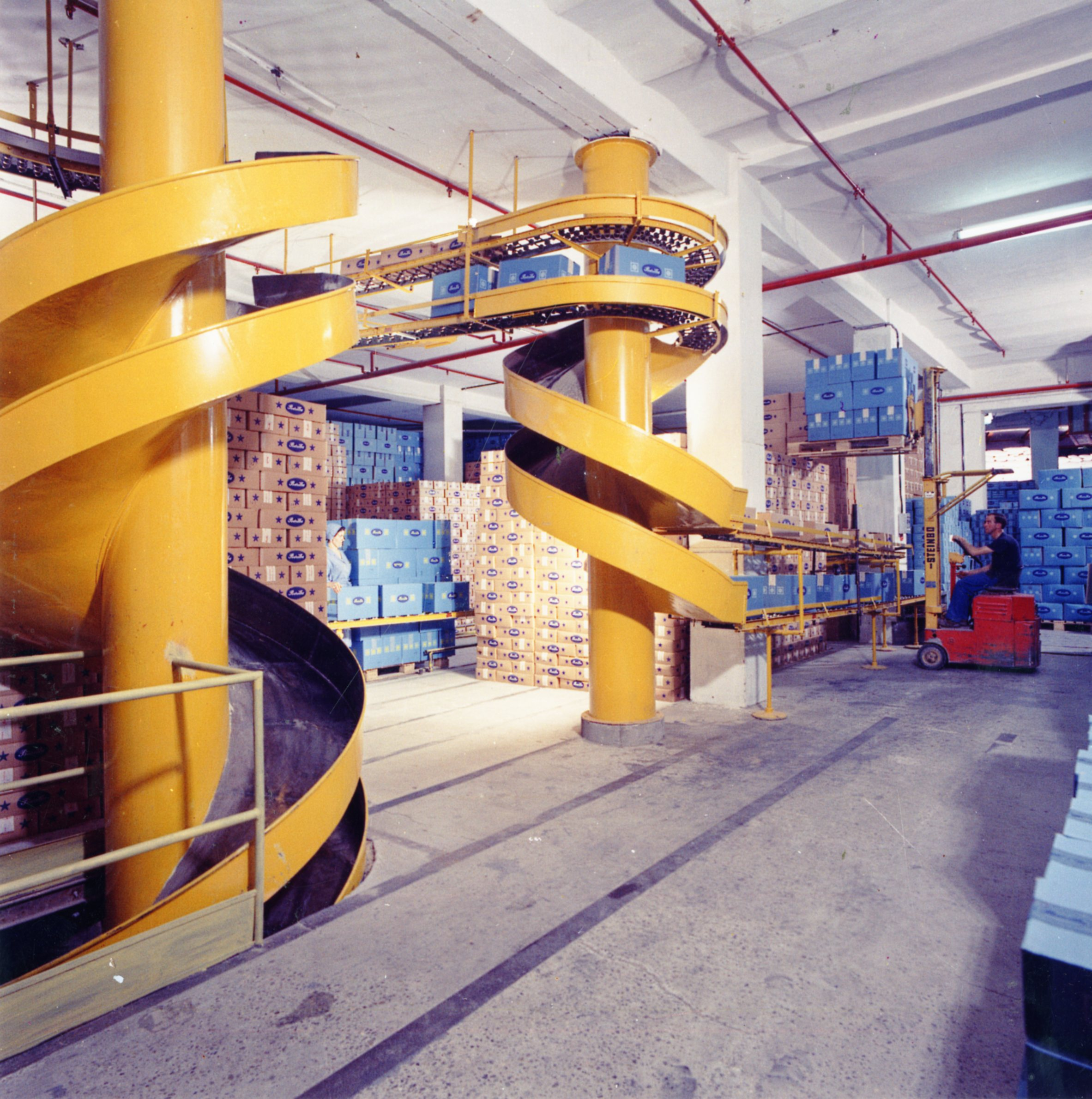 An inner view of the storage areas on ground level, characterized by helicoidal slipways to send down the packaged product in a photo by Bruno Vaghi dating from the early 1960s [ASB, O, Plants].