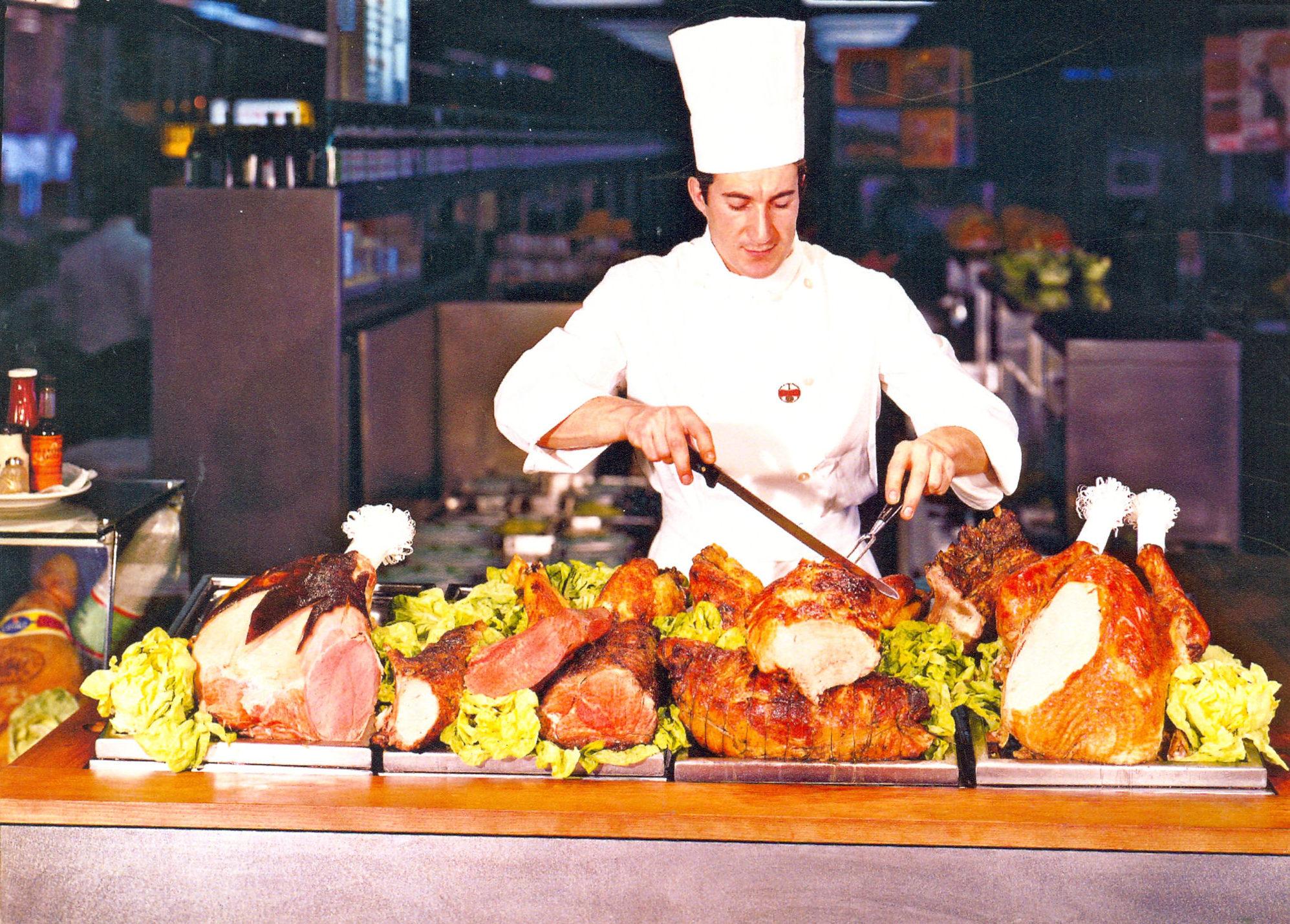 Cuoco di un Autogrill davanti al carrello degli arrosti