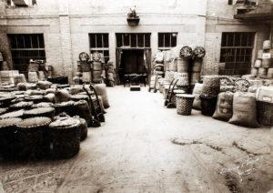 """Con la carta per alimenti venivano anche foderati i """"corbelli"""", cesti di scorza di castagno utilizzati per le spedizioni ai negozianti. Qui il Reparto Spedizioni Barilla nel 1911 in una foto di Luigi Vaghi con, in primo piano, numerosi corbelli pronti per la spedizione [ASB, BAR I A 29]."""