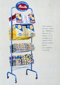 Espositore in filo metallico e tubolare con ruote e targa smaltata per la vendita del prodotto confezionato, diffuso nei negozi a partire dal 1956 [ASB, BAR, I, Ri, Espositori].
